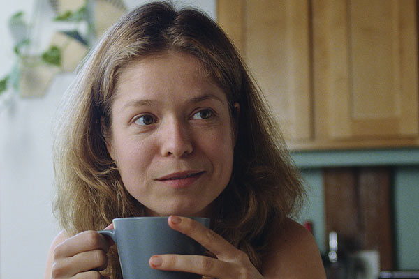 Film Still THE DEEP SKY von Regisseur, Autor, Produzent und Kameramann Frazer Bradshaw aus USA, 2017; Nina (gespielt von Luise Helm) sitzt am Küchentisch mit einer Tasse in der Hand