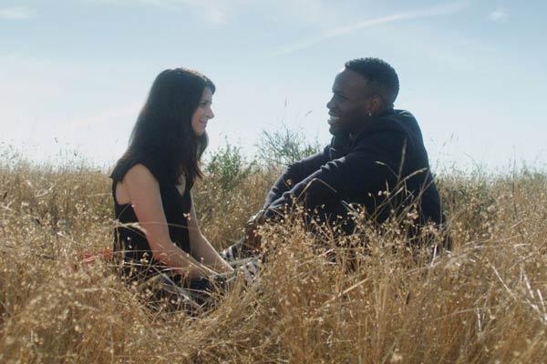 Film Still THE DEEP SKY von Regisseur, Autor, Produzent und Kameramann Frazer Bradshaw aus USA, 2017; Lenora (gespielt von Sarah Rose Butler) und ihr Partner Arlan (gespielt von Kelechi Nwadibia) sitzen zusammen in einer strohigen Wiese