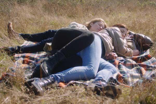 Film Still THE DEEP SKY von Regisseur, Autor, Produzent und Kameramann Frazer Bradshaw aus USA, 2017; Lenora (gespielt von Sarah Rose Butler) und Nina (gespielt von Luise Helm) liegen auf dem Bauch von Arlan (gespielt von Kelechi Nwadibia) in einer strohigen Wiese