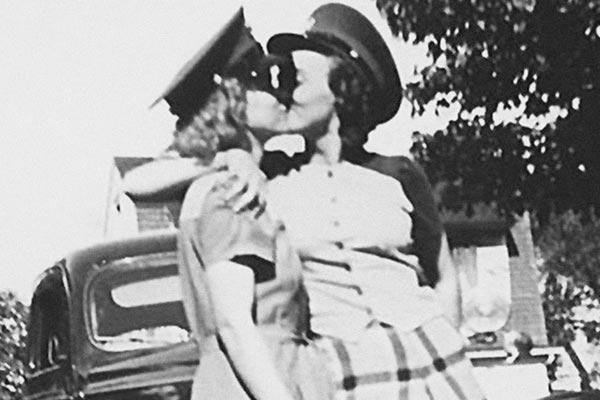 Film Still THE LAVENDER SCARE von Debüt-Regisseur Josh Howard aus USA, 2017, über Eisenhowers Hexenjagd auf homosexuelle US-Regierungsmitarbeiter; Silhuetten von zwei Frauen mit Schaffner-Kappen, die sich in den 1950ern vor einem Haus küssen