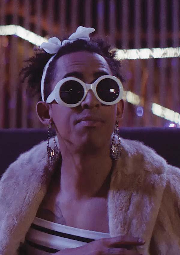 Film Still TUCKED von Autor und Regisseur Jamie Patterson aus England, 2018; Faith (gespielt von Jordan Stephens) sitzt stylisch mit weißer Sonnenbrille und Schleife im Haar vor der Neonbeleuchtung einer Strip-Bar