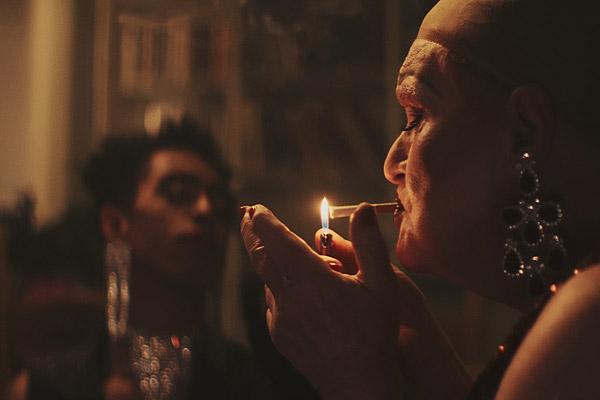 Film Still TUCKED von Autor und Regisseur Jamie Patterson aus England, 2018; die Drag-Queen Jackie (gespielt von Derren Nesbitt) zündet sich ohne Perücke eine Zigarette an und Faith (gespielt von Jordan Stephens) steht mit Diadem und großen Ohrringen im Hintergrund
