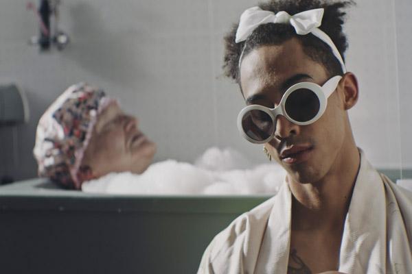 Film Still TUCKED von Autor und Regisseur Jamie Patterson aus England, 2018; die kaum geschminkte Drag-Queen Jackie (gespielt von Derren Nesbitt) liegt mit Badehaube in der Badewann und Faith (gespielt von Jordan Stephens) sitzt stylisch mit weißer Sonnenbrille und Schleife im Haar davor