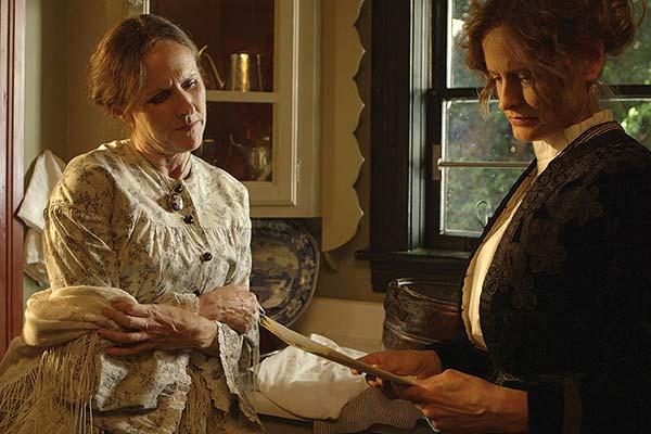 Film Still WILD NIGHTS WITH EMILY von Autorin und Regisseurin Madeleine Olnek über Schriftstellerin Emily Dickinson mit Amy Seimetz, Jackie Monahan; Emily (gespielt von Molly Shannon) steht in der Küche neben ihrer Schwägerin Susan (gespielt von Susan Ziegler), die einen ihrer Texte liest